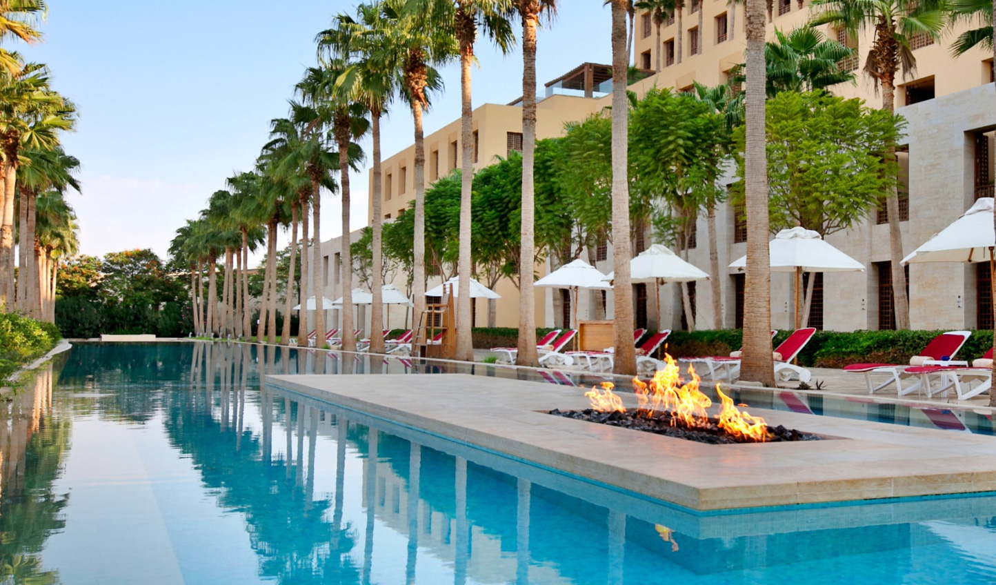 Relax by the palm-fringed pool at Kempinski Hotel Ishtar