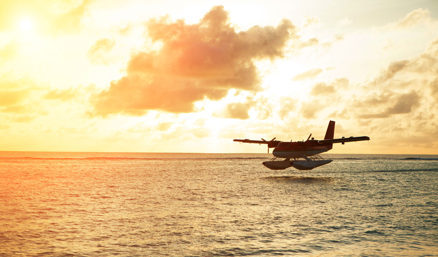 A seaplane soars above the water