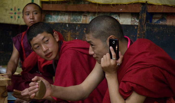 Bhutanese monks taking a break from their studies on their mobile phones