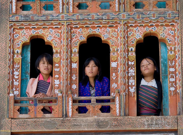 three bhutanese children looking out of the window