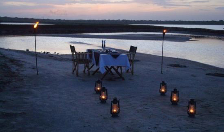 A fully laid, torch-lit table outside set for dinner at Mahoora Safari Camp, Sri Lanka
