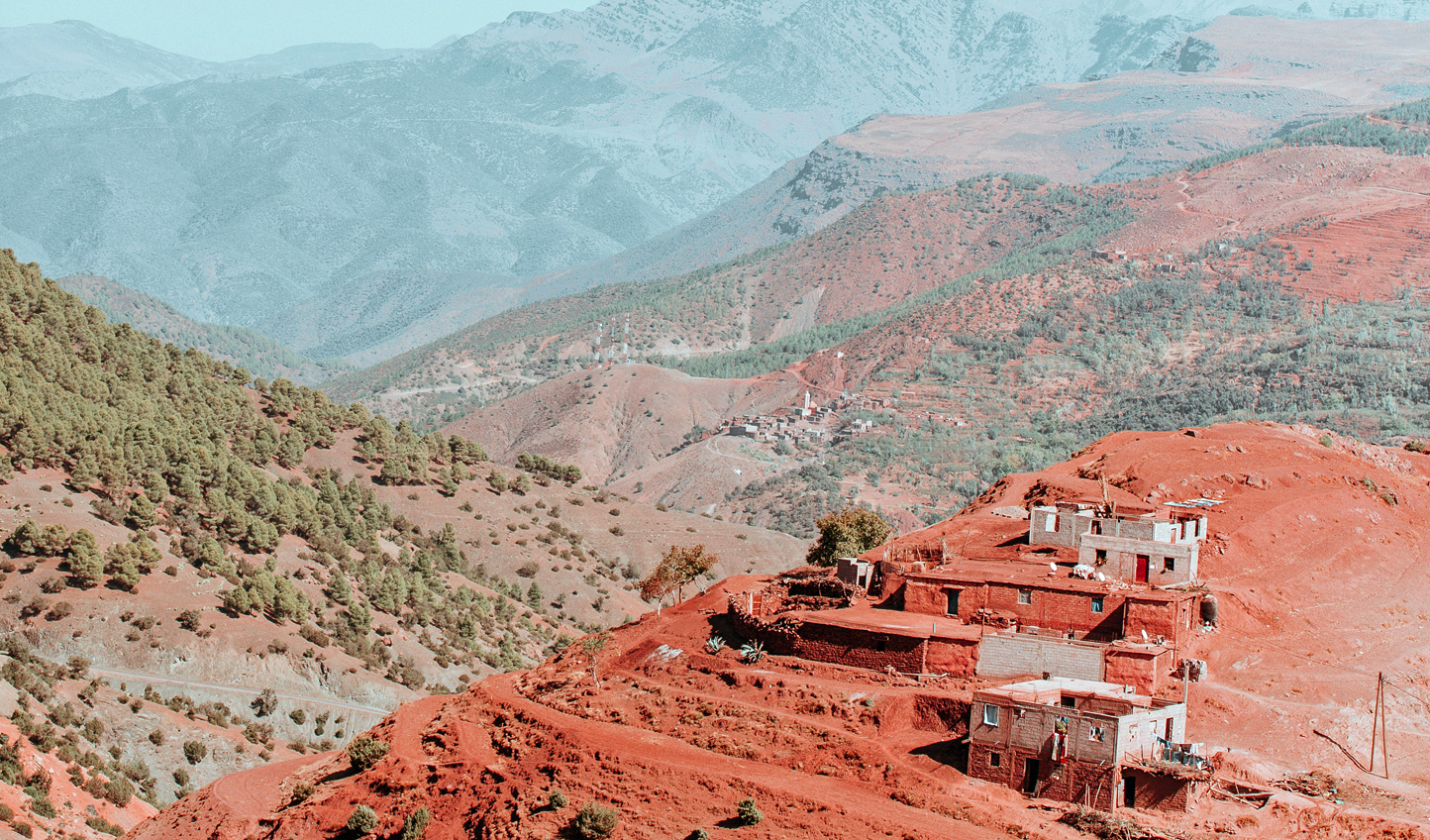 Valleys carve their way through the Atlas Mountains with isolated houses clinging to their sides