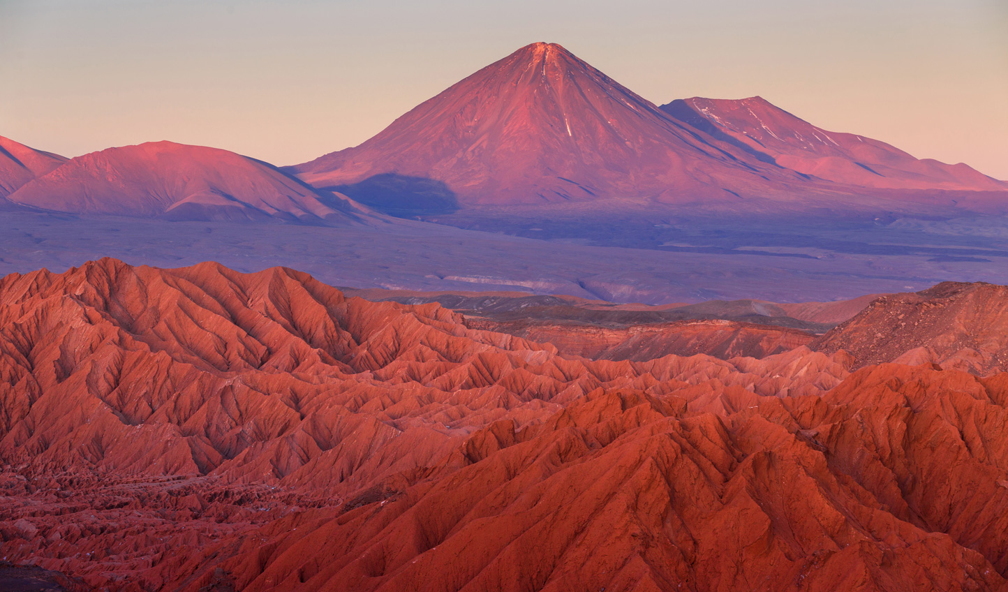 Watch the way the sun paints the desert mountains pink and orange