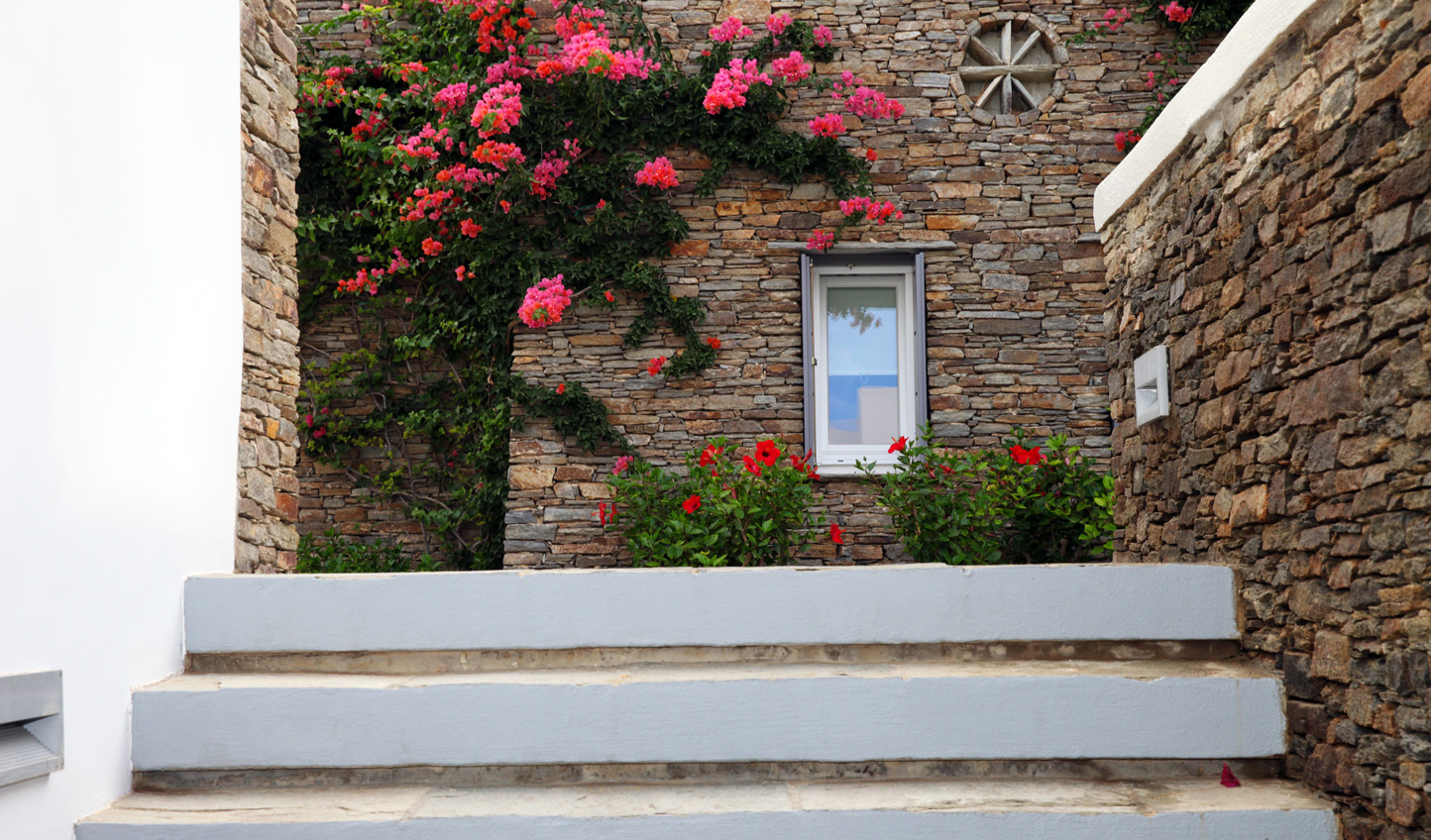 Quaint stone buildings and brightly coloured flowers await