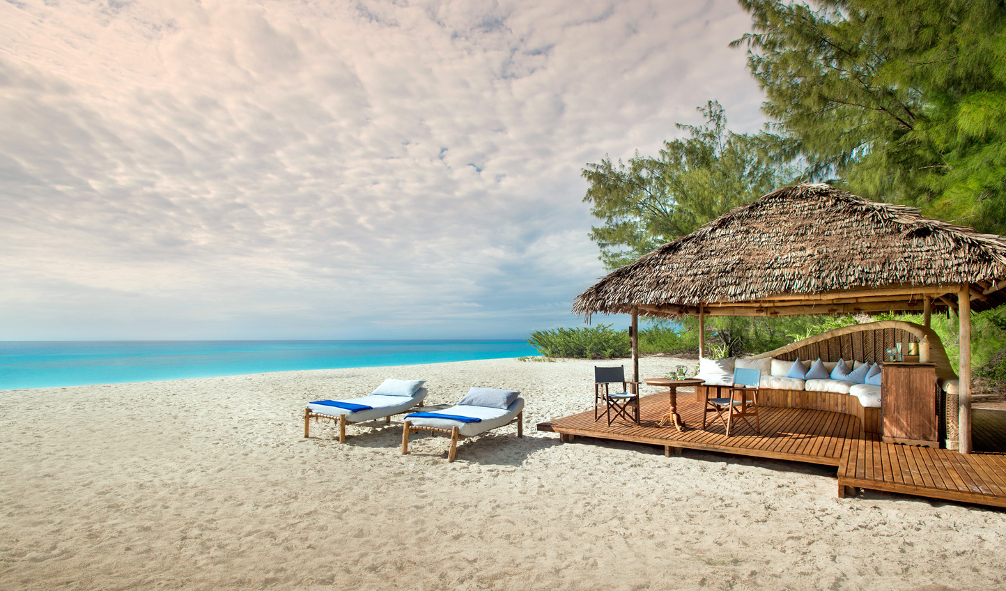 Laze under the beach cabana at Mnemba Island Lodge