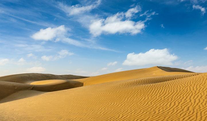 Enjoy a camel safari through the Sam Sand Dunes