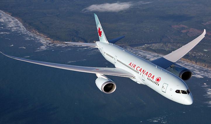 An Air Canada plane flying along a coastline