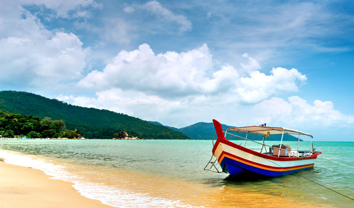 Admire the stunning beaches and colorful boats at Penang
