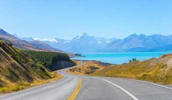 A road winds alongside a glistening lake in New Zealand