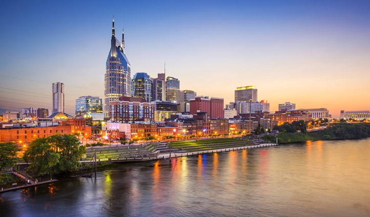 Nashville's lights reflect off the water at sunset
