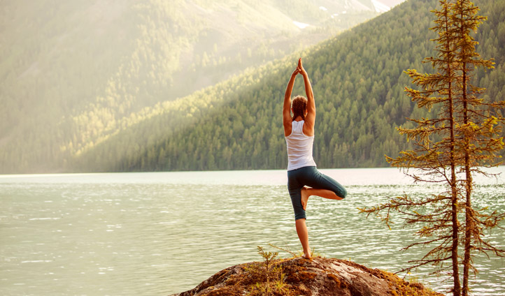 A yogi practices her stances by a mountain lake in Canada