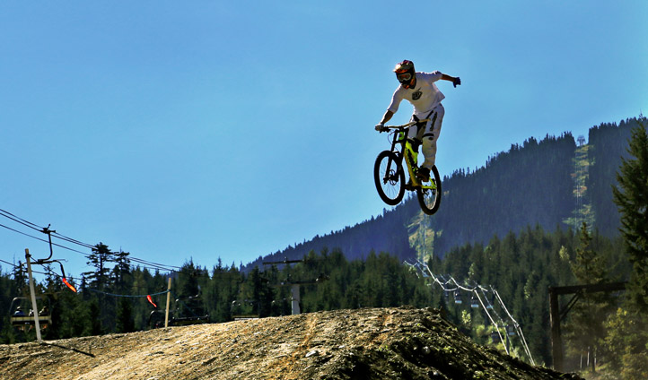 A mountain-biker tackles a jump in Whistler, Canada