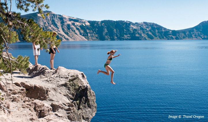 A lady takes a leap into an alpine lake in Oregon