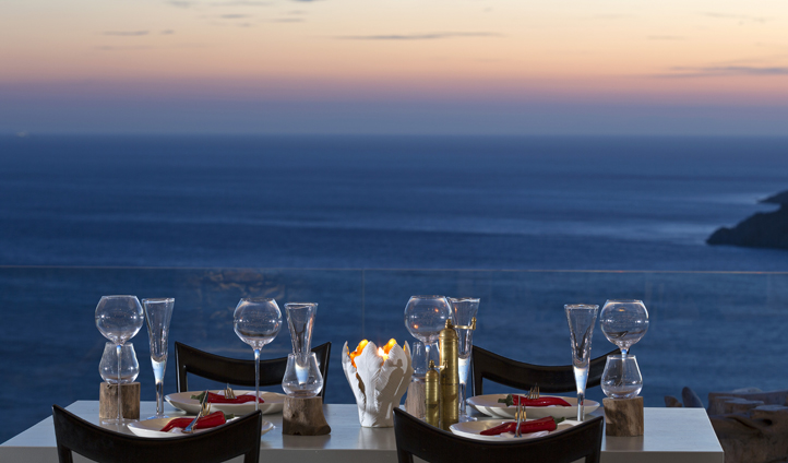 Dine under the night sky as the sun slips away into the Aegean