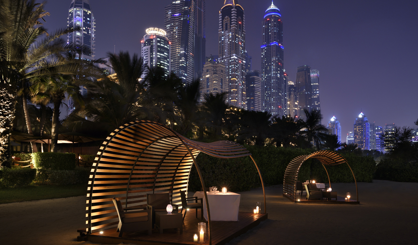 Dine with your toes in the sand and glittering city lights overhead