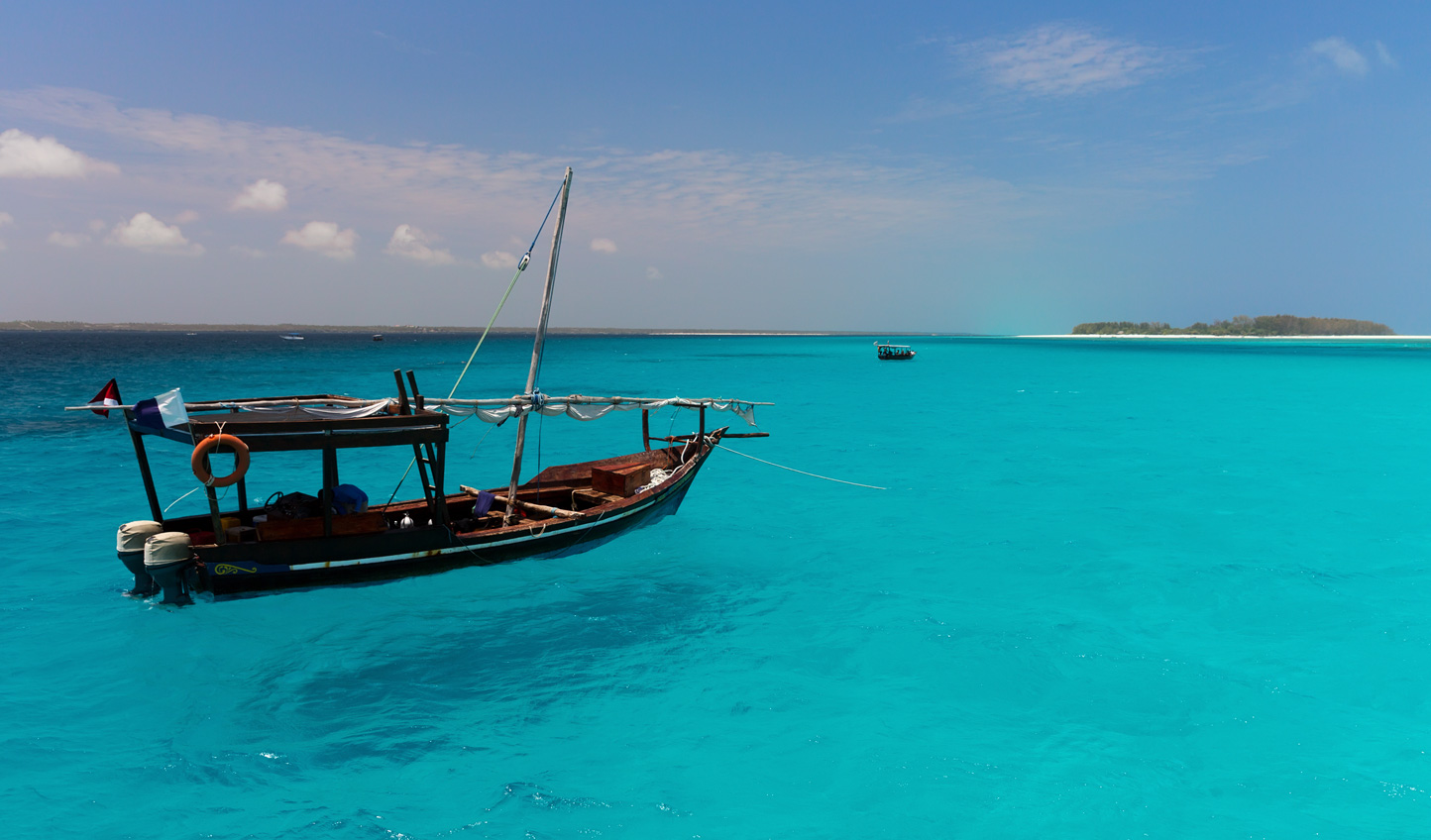 Sail across crystal clear waters from Mnemba Island