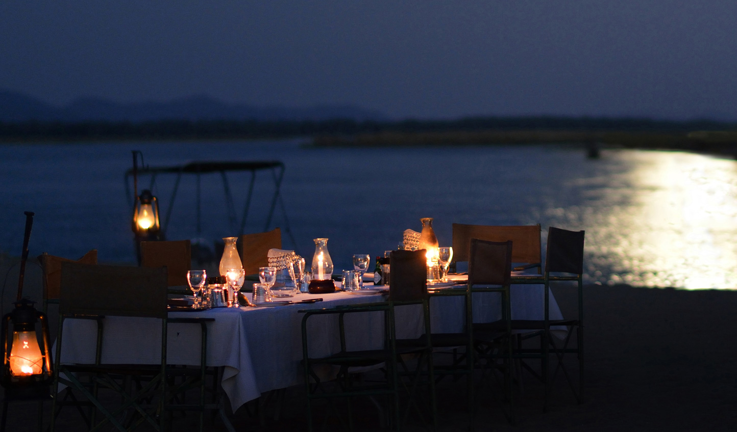 Dine by moonlight on the banks of the Zambezi