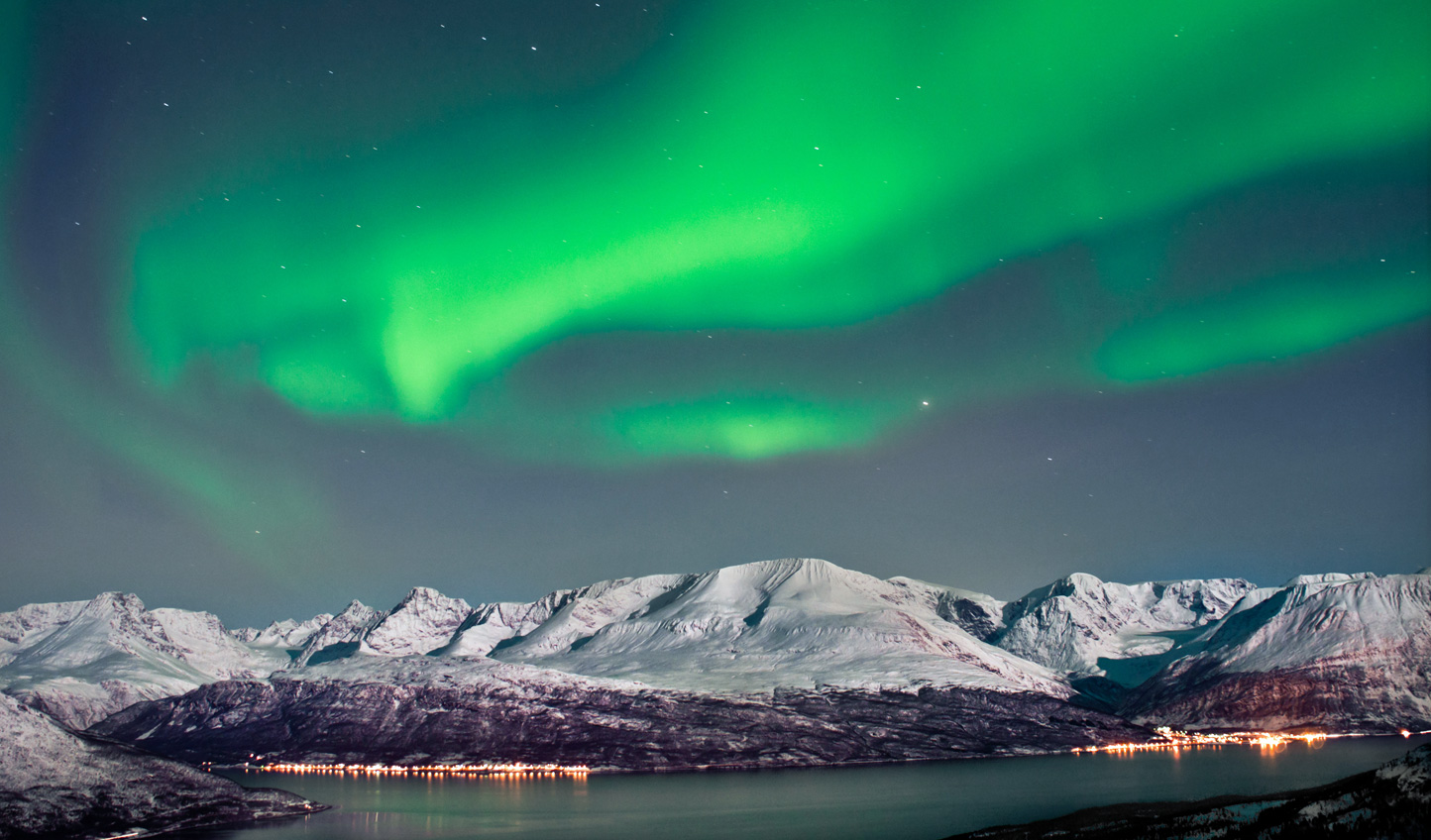 By night, watch the flicker of the Northern Lights over the fjords