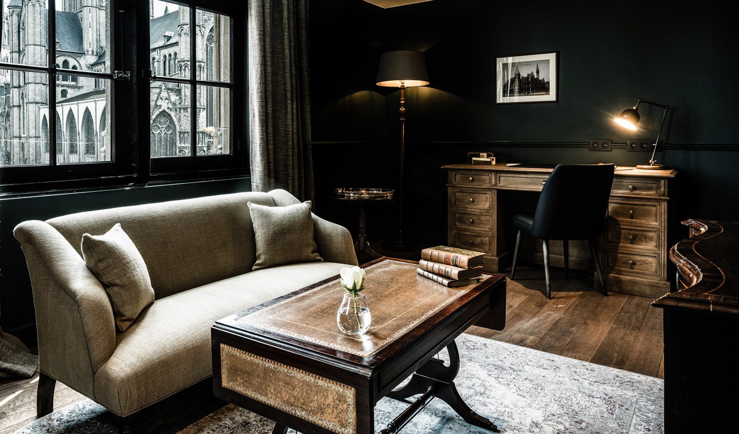 Photography of Ghent and antique pieces are draped around the spaces, echoing the style of the building's historic architecture